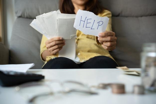 Jonge aziatische vrouw bezorgd hulp nodig bij stress thuis, boekhoudkundige schulden rekeningen bankkosten uitgaven en betalingen wanhopig voelen in slechte financiële situatie. detailopname