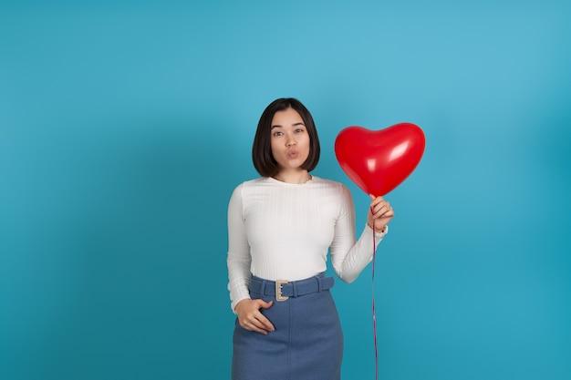 Jonge aziatische vrouw blaast een kus en houdt een rode hartvormige ballon vast
