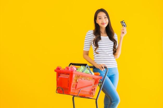 Jonge aziatische vrouw boodschappen kar van supermarkt