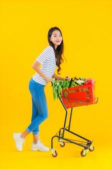 Jonge aziatische vrouw boodschappen kruidenier van supermarkt en kar