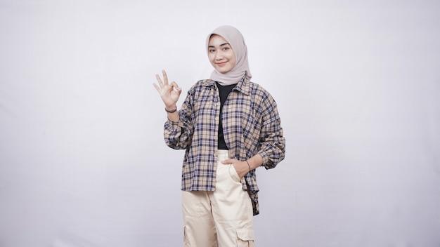 Jonge aziatische vrouw casual stijl handen in zak gebaar oke geïsoleerd op witte achtergrond