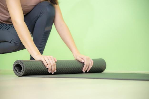 Jonge aziatische vrouw concentreert zich op rollende zwarte yogamat na yogales