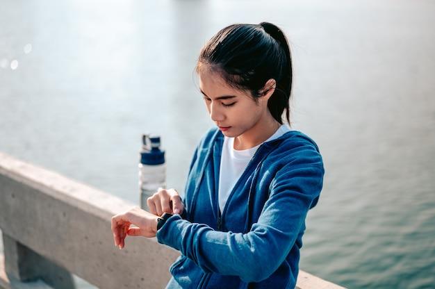 Jonge aziatische vrouw controleert de pols via een smartwatch na het joggen van een ochtendtraining in de stad