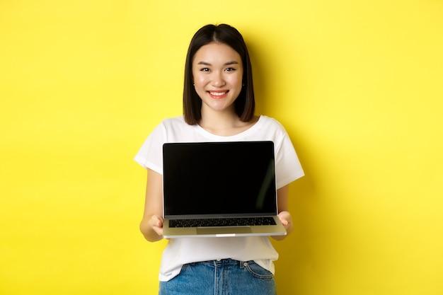 Jonge aziatische vrouw demonstreert online aanbod, toont laptopscherm en glimlacht, staande over gele achtergrond