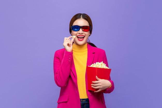 Jonge aziatische vrouw die 3d glazen draagt die etend popcorn en het letten op film genieten van