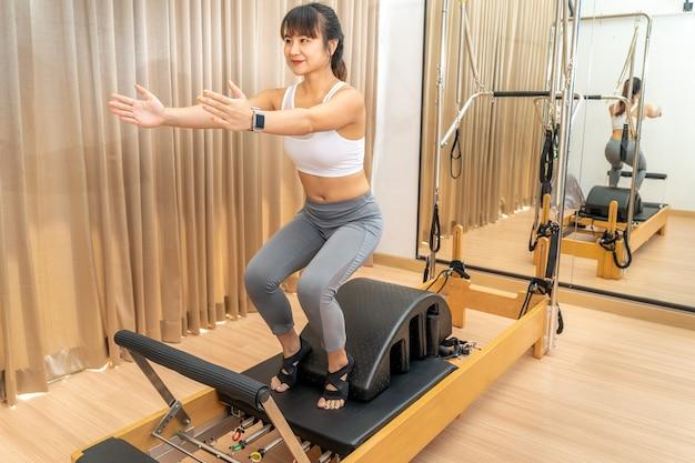 Jonge aziatische vrouw die aan de machine van de pilateshervormer werkt tijdens gezondheidsoefening in haar sportschool