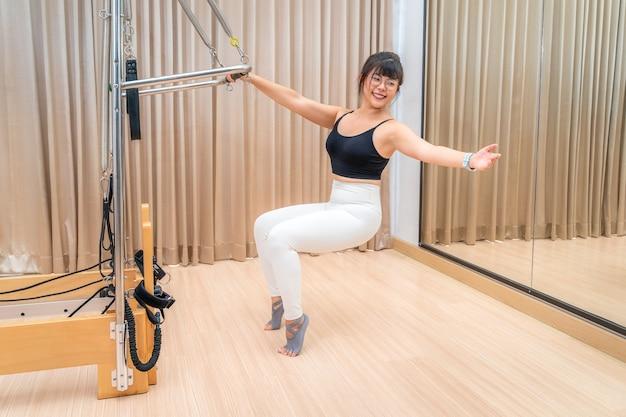 Jonge aziatische vrouw die aan de pilates-reformer-machine werkt tijdens haar gezondheidstraining