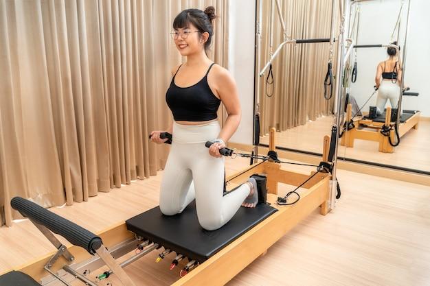 Jonge aziatische vrouw die aan de pilates-reformer-machine werkt tijdens haar training voor gezondheidsoefeningen