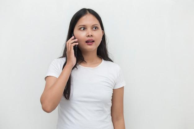 Jonge aziatische vrouw die aan de telefoon spreekt