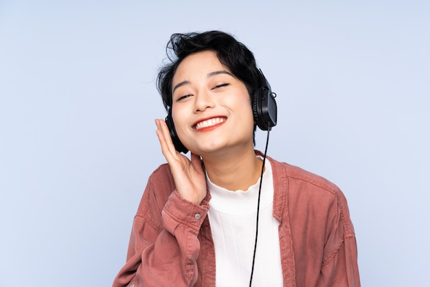 Jonge aziatische vrouw die aan muziek luistert