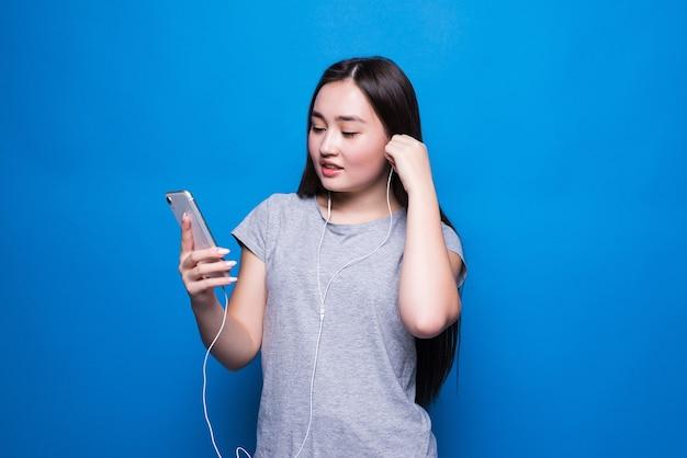Jonge aziatische vrouw die aan muziek met rode hoofdtelefoons in blauwe naadloze muur luistert. entertainment, muziekapplicatie, online stomen
