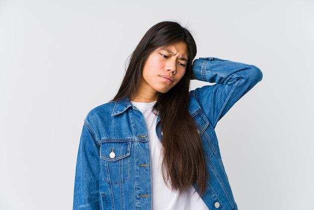 Jonge aziatische vrouw die aan nekpijn lijdt vanwege een zittende levensstijl.