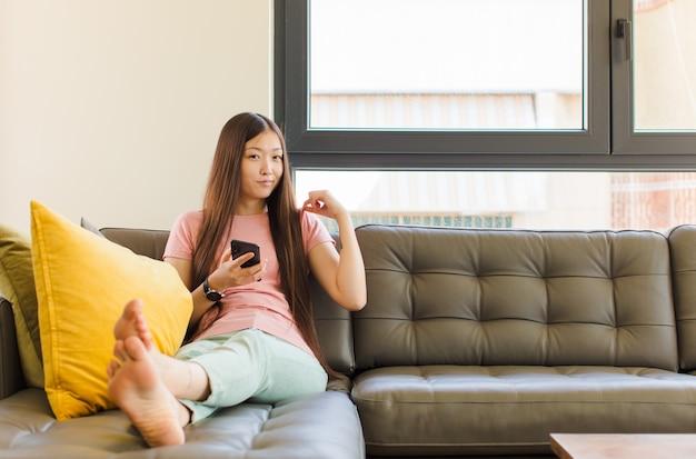 Jonge aziatische vrouw die arrogant, succesvol, positief en trots kijkt, wijzend naar zichzelf