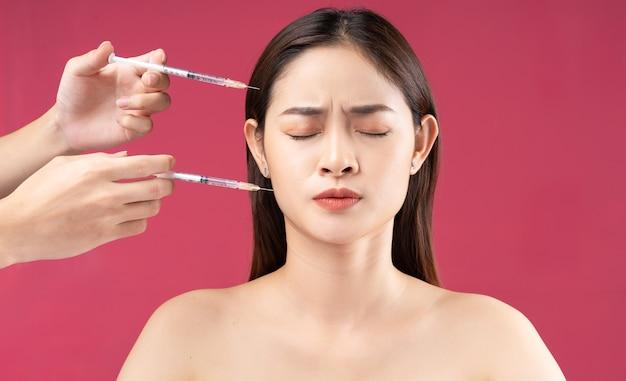 Jonge aziatische vrouw die bang is bij het injecteren van vulmiddel