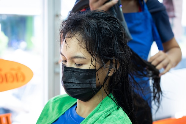 Jonge aziatische vrouw die beschermingsmasker draagt die een drogend haar met föhn krijgt door kapper bij kapsalon. kapper die haar aan cliënt droogt. schoonheidssalon, haarverzorgingsconcept.