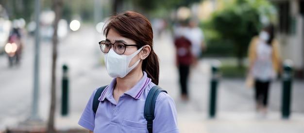 Jonge aziatische vrouw die beschermingsmasker draagt tegen griepvirus in de stad. gezondheidszorg en luchtvervuiling concept