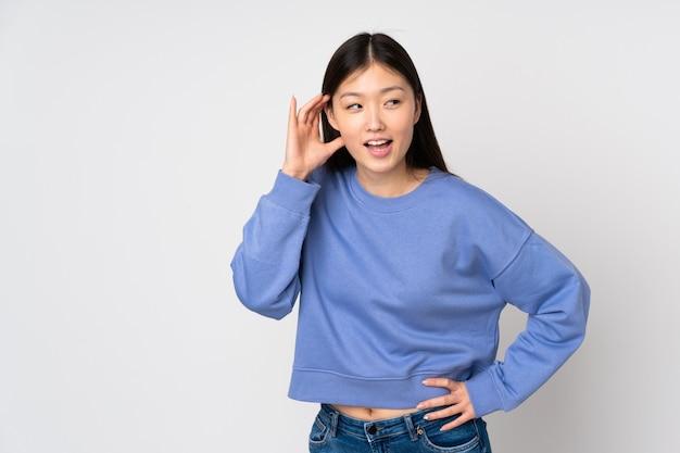 Jonge aziatische vrouw die bij het luisteren aan iets wordt geïsoleerd door hand op het oor te zetten