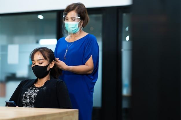 Jonge aziatische vrouw die bij kapsalon chirurgisch beschermend gezichtsmasker draagt. nieuw normaal en sociaal afstandsconcept