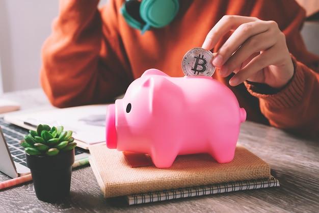 Jonge aziatische vrouw die bitcoin-muntstuk zetten in roze spaarvarken voor het besparen van het beheer van de geldrijkdom - economisch financiënconcept