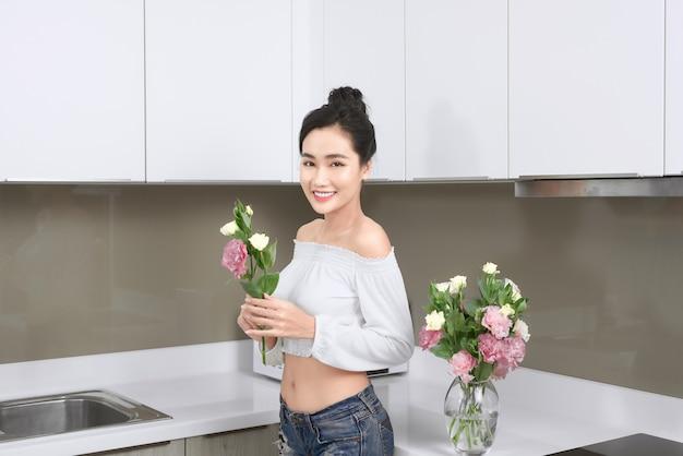 Jonge aziatische vrouw die bloemen in de keuken schikt.