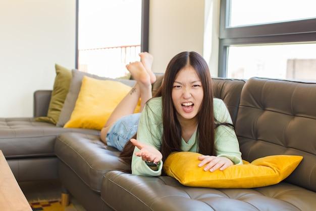 Jonge aziatische vrouw die boos, geïrriteerd en gefrustreerd kijkt, schreeuwend wtf of wat is er mis met je