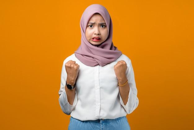 Jonge aziatische vrouw die boos op geel voelt
