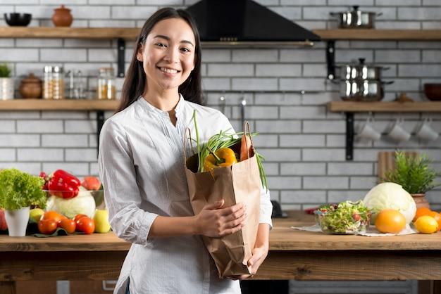 Jonge aziatische vrouw die bruine kruidenierswinkelzak met groenten houdt