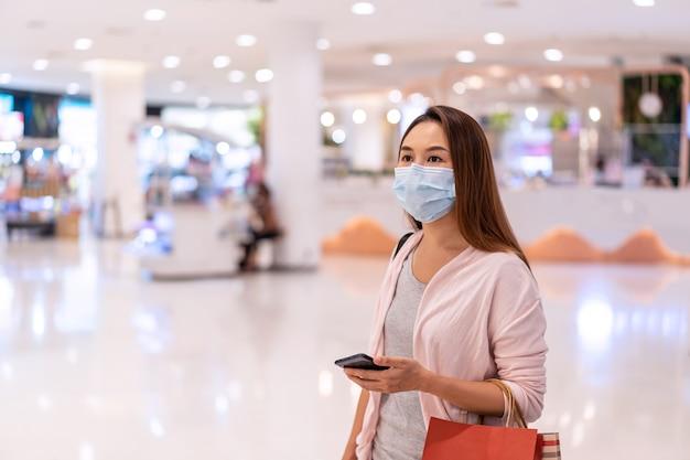 Jonge aziatische vrouw die chirurgisch masker draagt dat in klerenopslag bij wandelgalerij winkelt
