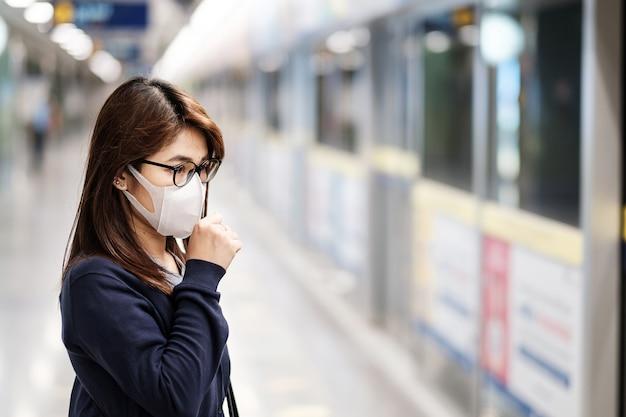 Jonge aziatische vrouw die chirurgisch masker draagt