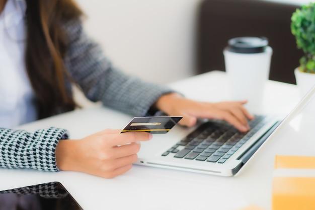 Jonge aziatische vrouw die creditcard met laptop gebruikt om online te winkelen