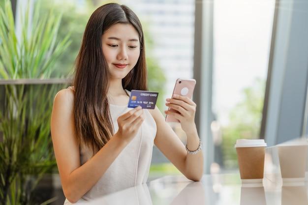 Jonge aziatische vrouw die creditcard met mobiele telefoon voor online het winkelen gebruikt