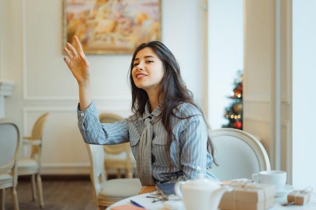 Jonge aziatische vrouw die de serveerster in koffie roept