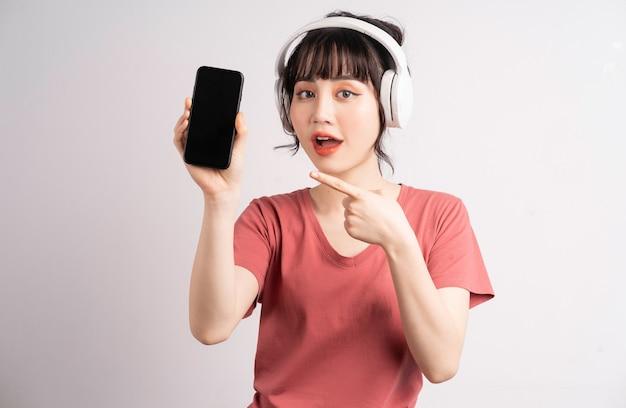 Jonge aziatische vrouw die draadloze hoofdtelefoon gebruikt om muziek te luisteren