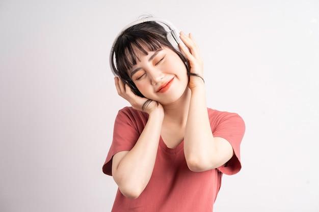 Jonge aziatische vrouw die draadloze hoofdtelefoons draagt om muziek op wit te luisteren
