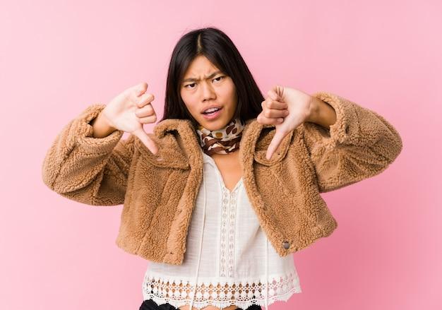 Jonge aziatische vrouw die duim tonen en afkeer uitdrukken.