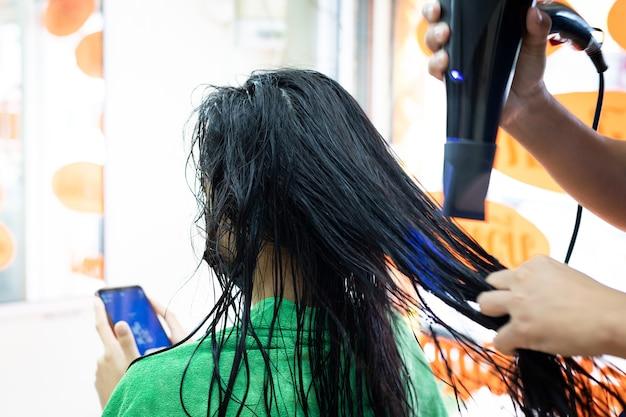 Jonge aziatische vrouw die een beschermingsmasker draagt en een smartphone gebruikt terwijl ze een drooghaar met een föhn krijgt bij de kapper. kapper die haar droogt aan cliënt bij kapsalon.