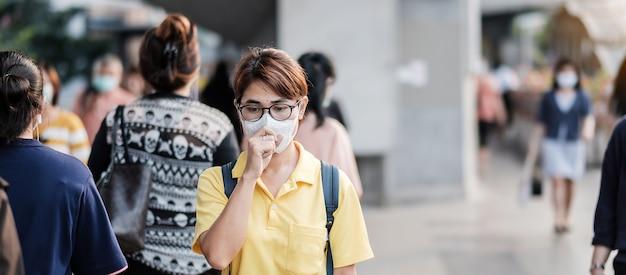 Jonge aziatische vrouw die een beschermingsmasker draagt tegen het nieuwe coronavirus (2019-ncov) of het wuhan-coronavirus op het openbare treinstation, is een besmettelijk virus dat infecties van de luchtwegen veroorzaakt.