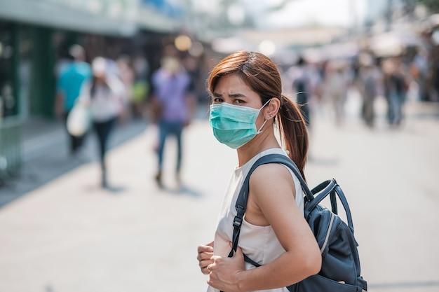Jonge aziatische vrouw die een beschermingsmasker draagt tegen novel coronavirus (2019-ncov) of wuhan coronavirus op chatuchak weekend market, bezienswaardigheid en populair voor toeristische attracties