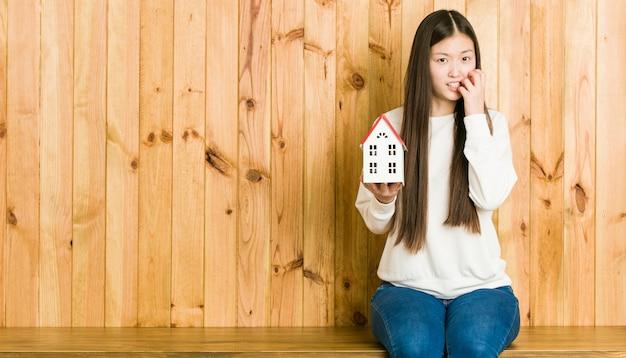 Jonge aziatische vrouw die een bijtende vingernagels van het huispictogram houdt, zenuwachtig en zeer bezorgd.
