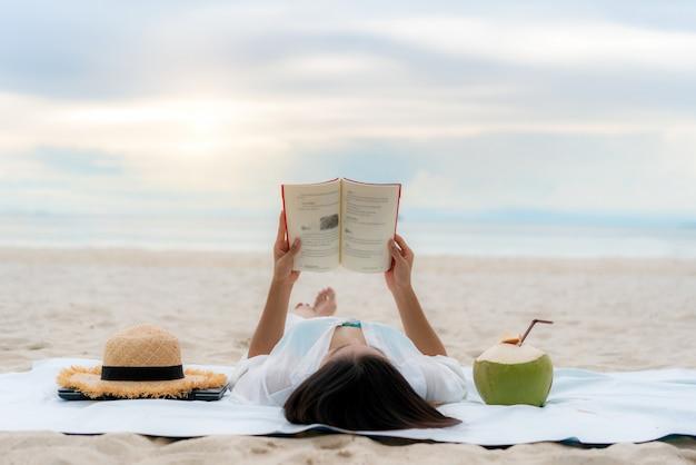 Jonge aziatische vrouw die een boek op het strand leest