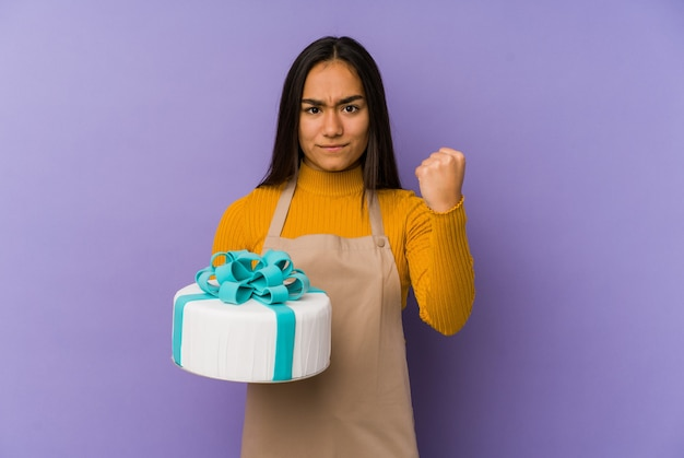 Jonge aziatische vrouw die een cake houdt