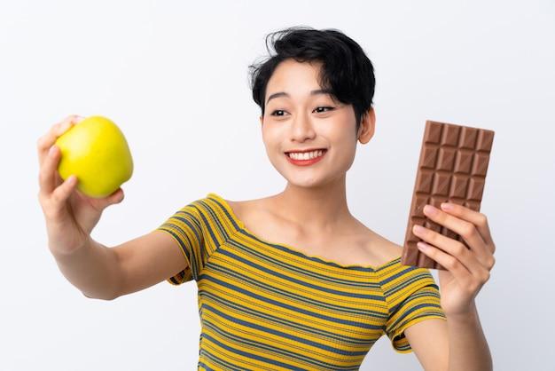 Jonge aziatische vrouw die een chocoladetablet in één hand neemt en een appel in de andere