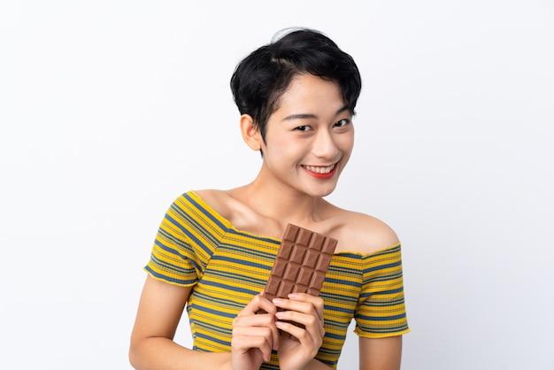 Jonge aziatische vrouw die een chocoladetablet neemt en gelukkig