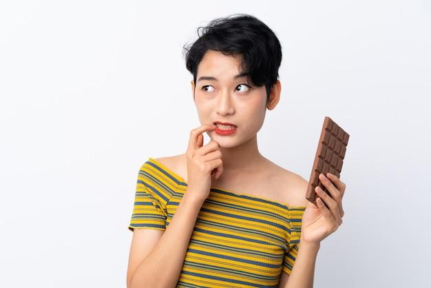Jonge aziatische vrouw die een chocoladetablet neemt en twijfels heeft