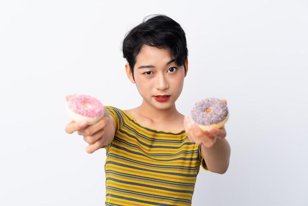 Jonge aziatische vrouw die een doughnut houdt en droevig
