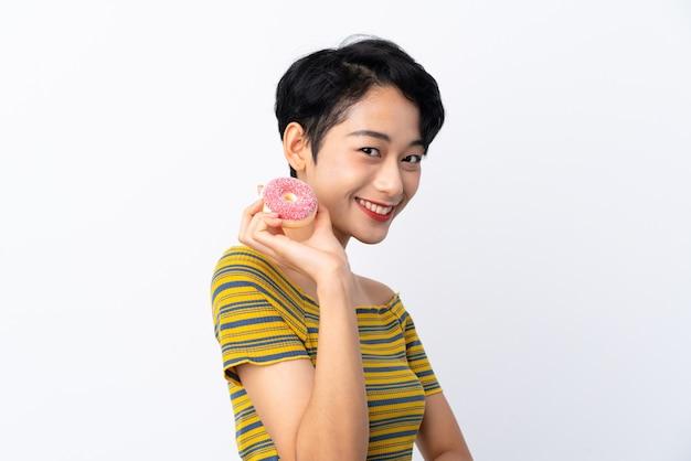 Jonge aziatische vrouw die een doughnut houdt en gelukkig