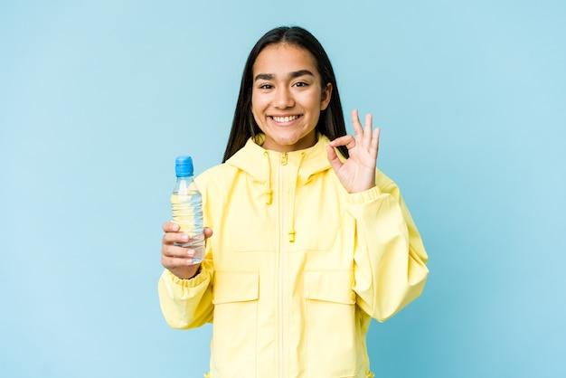 Jonge aziatische vrouw die een fles water houdt dat op blauw wordt geïsoleerd vrolijk en zeker die ok gebaar toont.