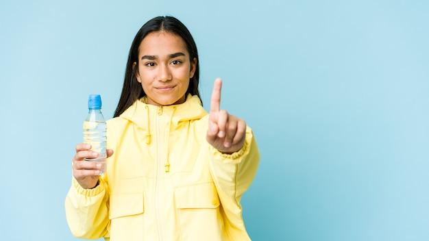 Jonge aziatische vrouw die een fles water houdt dat op blauwe muur wordt geïsoleerd die nummer één met vinger toont.