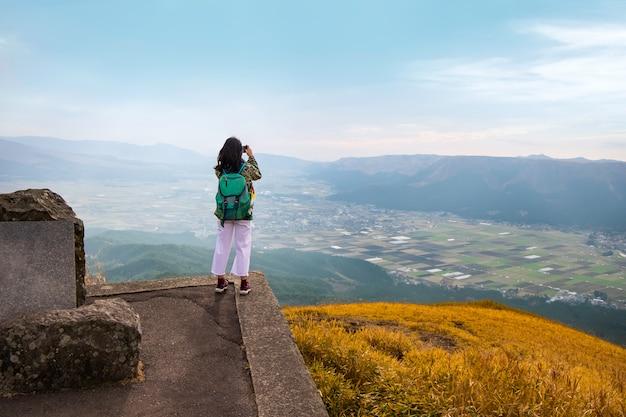 Jonge aziatische vrouw die een foto bovenop een berg met mooi uitzicht neemt