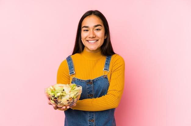Jonge aziatische vrouw die een geïsoleerde salade houdt die lacht en pret heeft.